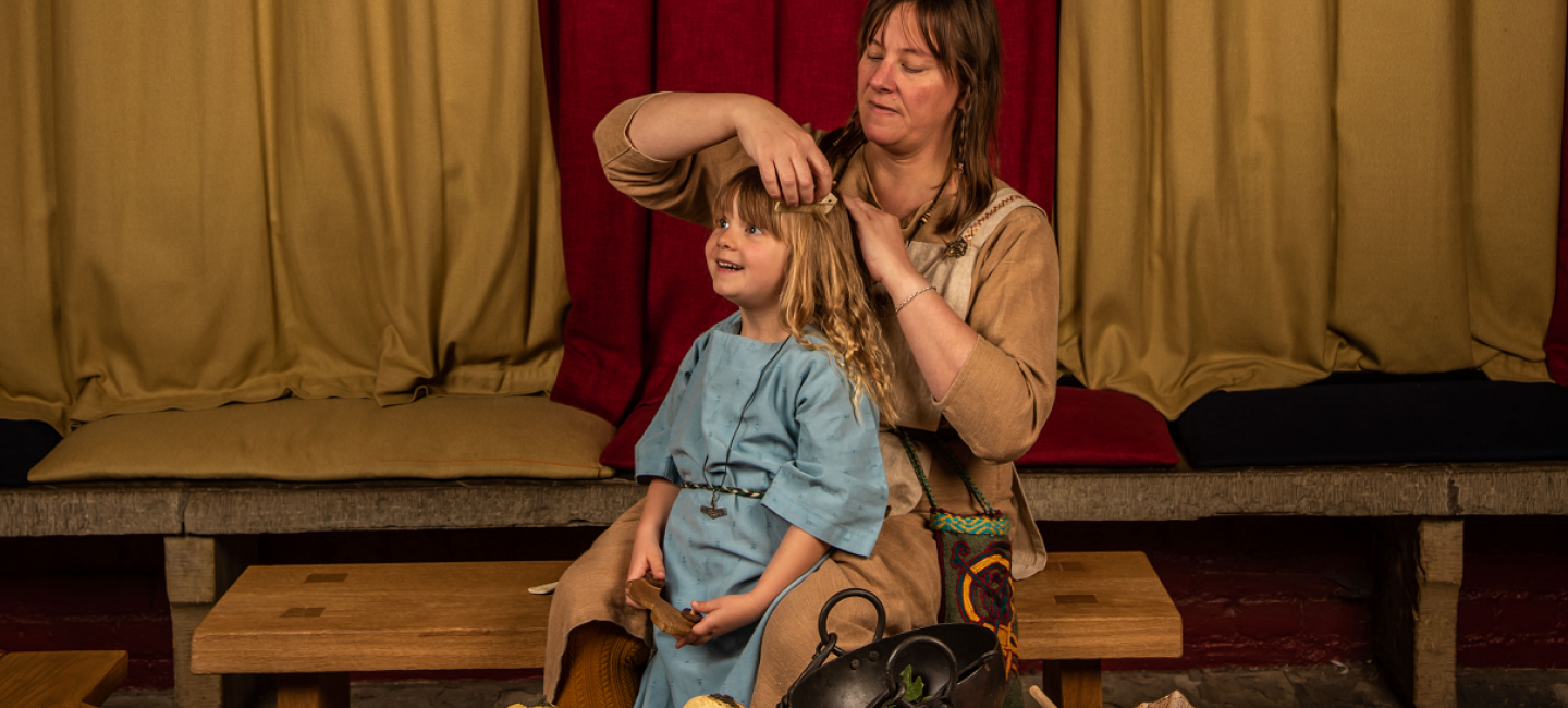 Lady combing girl's hair, both dressed in Viking-style clothes