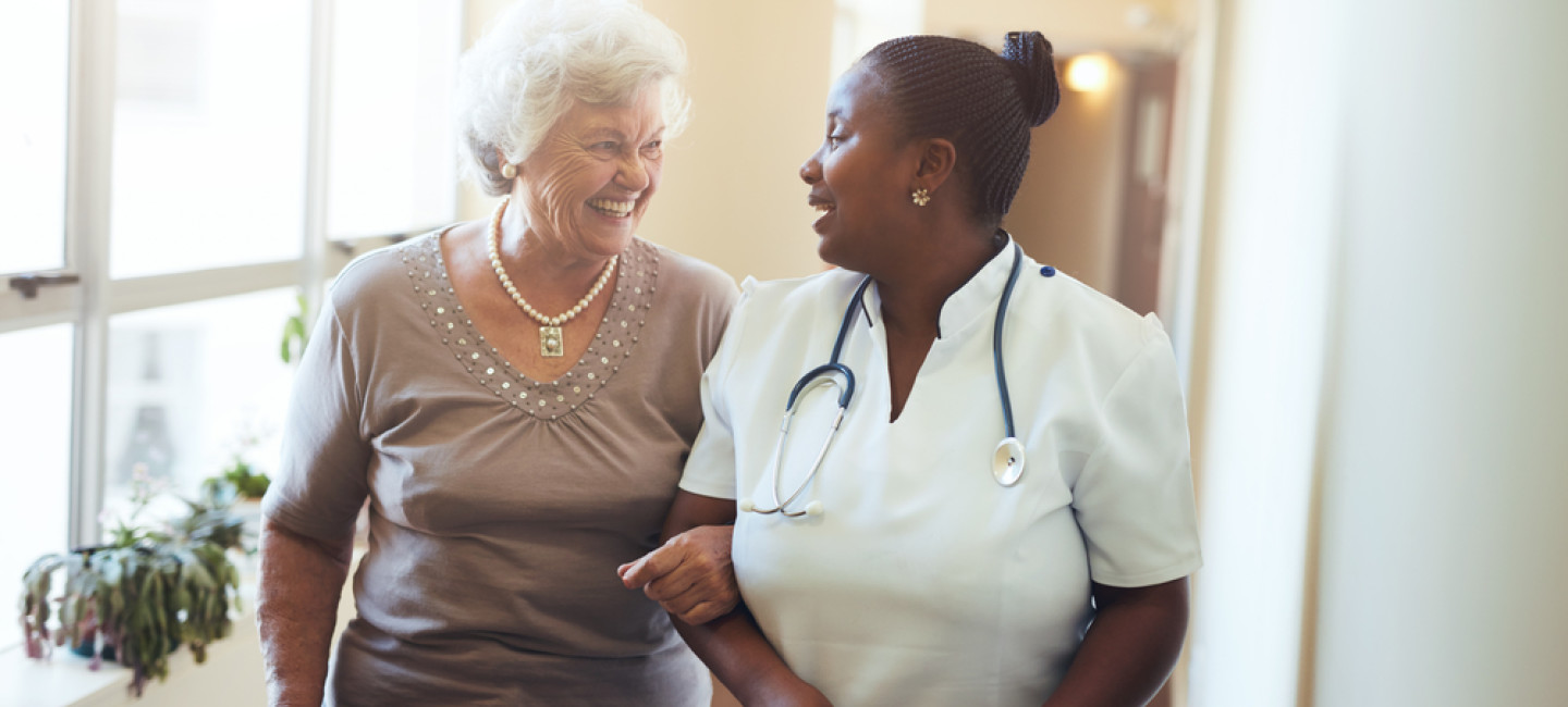 Nurse with elderly patient walking through sunny corridor