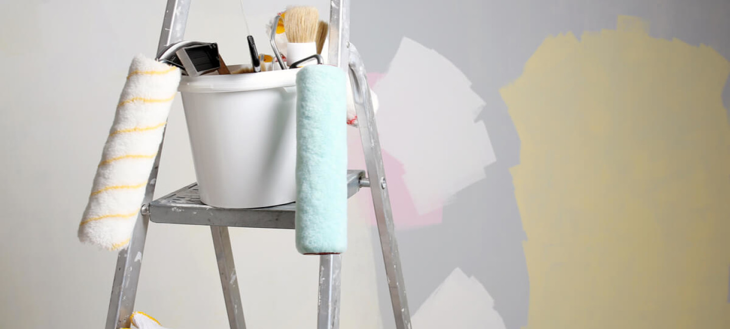 Half decorated room with paint swatches on walls and ladder with decorating equipment