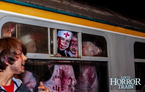 Zombie actors peering out of a train window at Loco Horror Train
