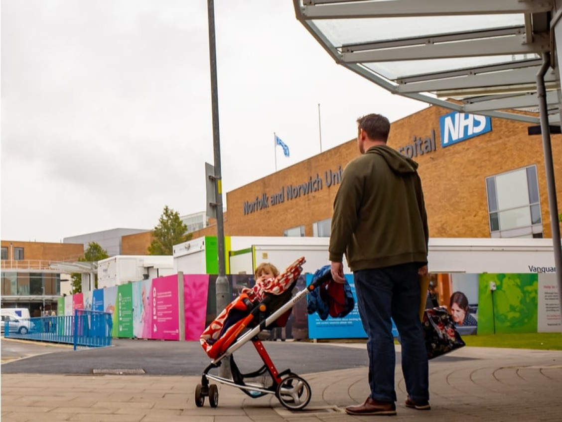 Man with daughter in pushchair outside Norfolk and Norwich Hospital